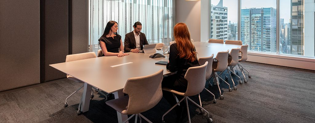 A large Regus meeting room with two women and a man sat at the table