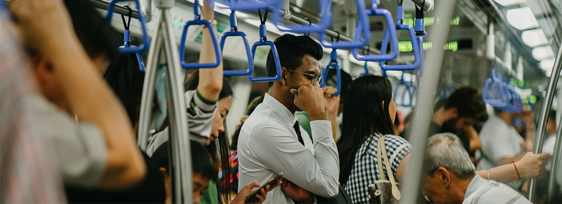 A man stood on bust public transport, such as a metro service